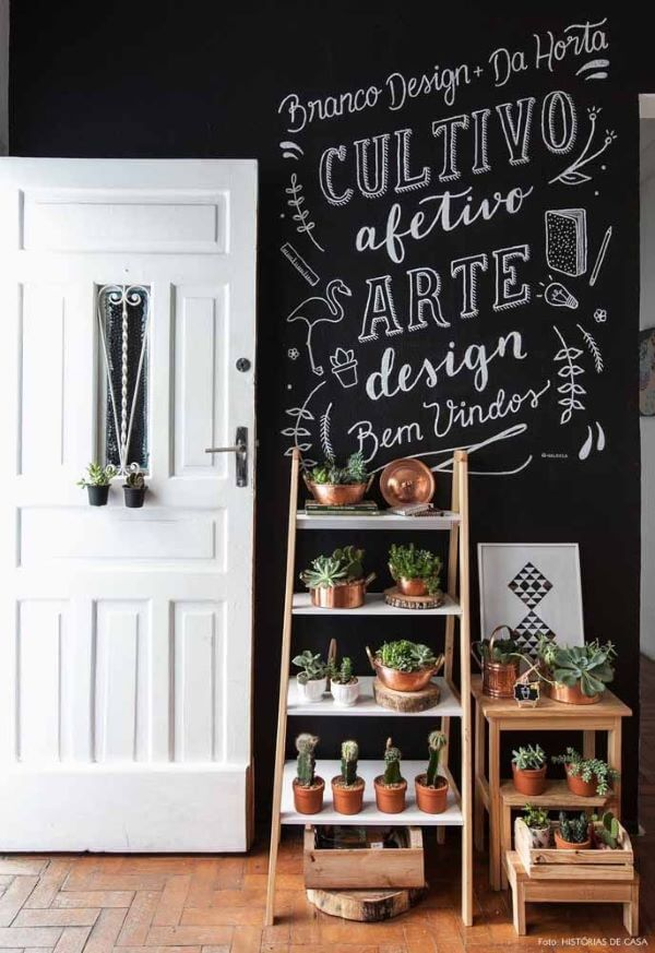 Entrada de casa com lettering e mini estante para plantas