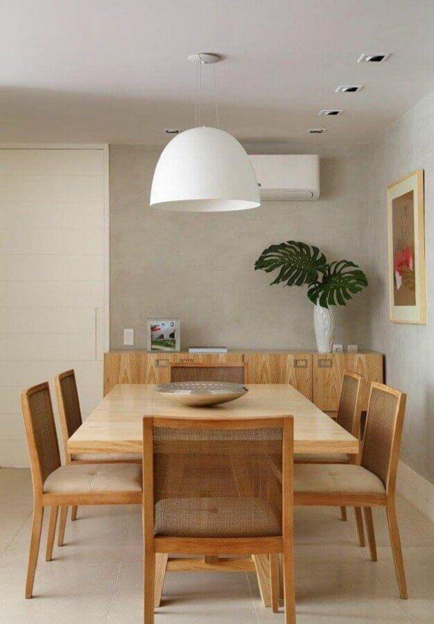 Luminária branca para decoração moderna de sala de jantar com buffet de madeira e parede de cimento queimado  Foto MCA Estudio