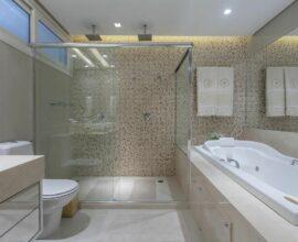 O espelho em cima da banheira simples de hidromassagem traz a sensação de amplitude no cômodo. Fonte: Vanja Maia