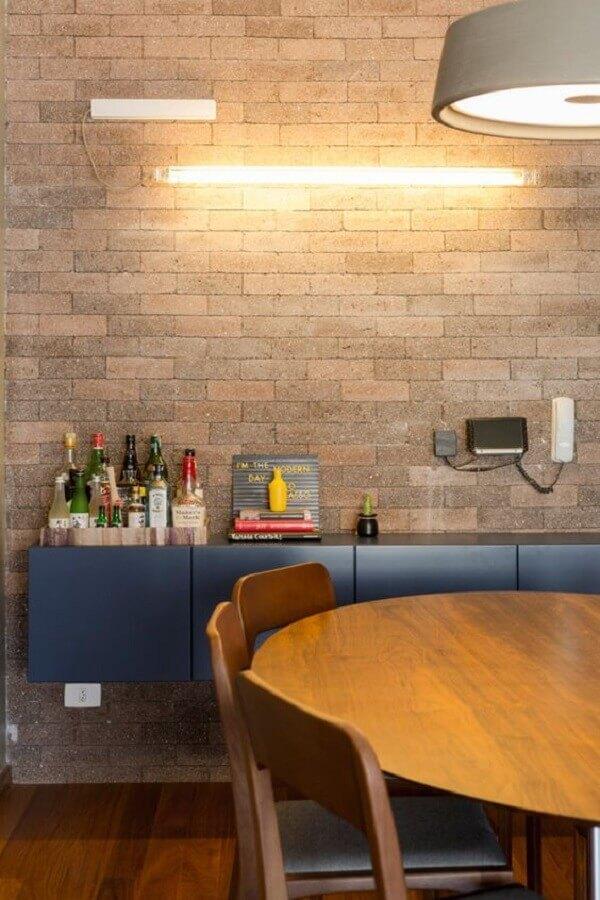 Parede de tijolinho para decoração de sala de jantar com buffet azul e mesa de madeira Foto Design Milk
