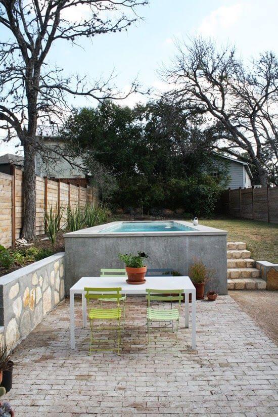 Piscina elevada no jardim moderno com mesa para receber amigos bem charmosa
