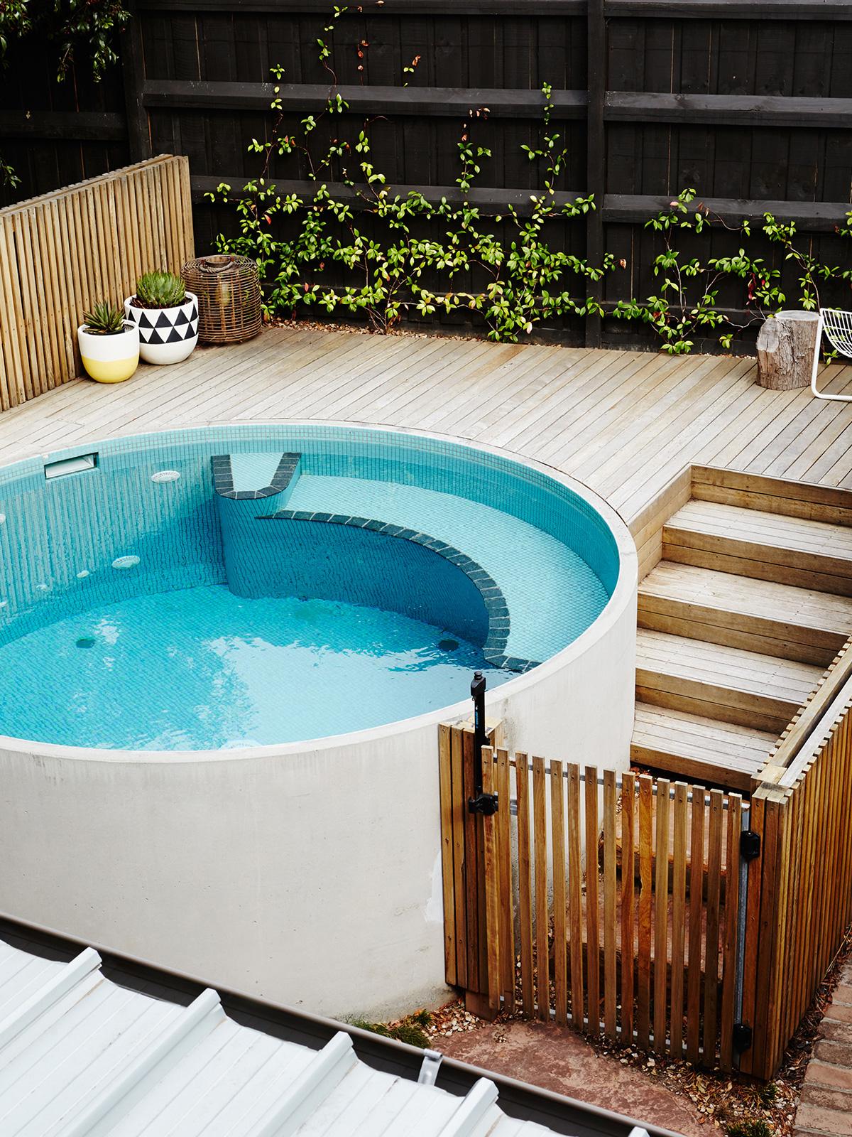 Quintal pequeno com piscina redonda elevada e portão para evitar a entrada de crianças
