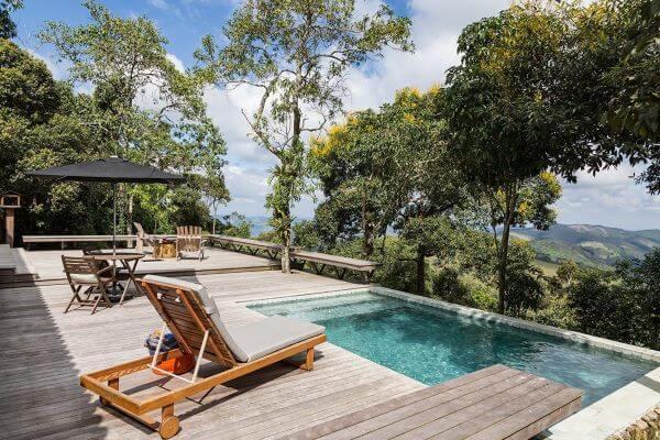 Quintal com piscina de borda infinita e deck de madeira