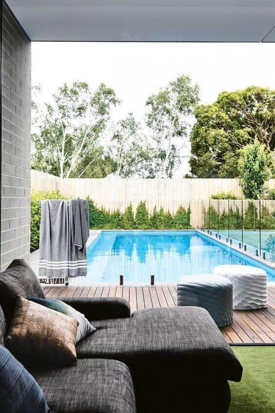 Quintal com piscina de fibra e deck de madeira decorado com puffs