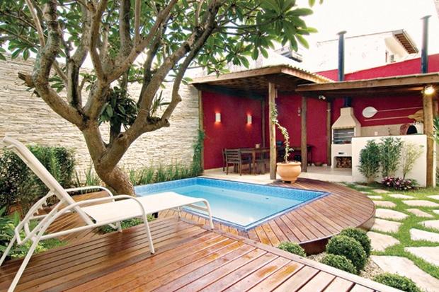 Quintal com piscina de fibra pequena e churrasqueira na área gourmet