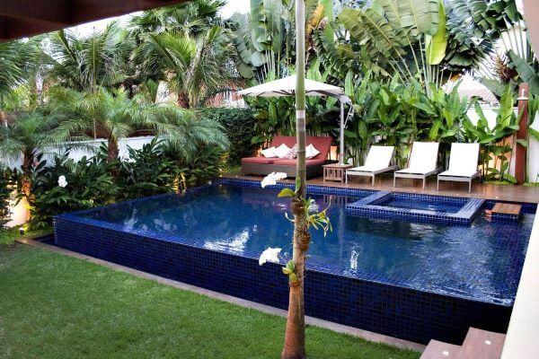 Quintal com piscina e chaise na área externa vermelha decorada com almofadas modernas
