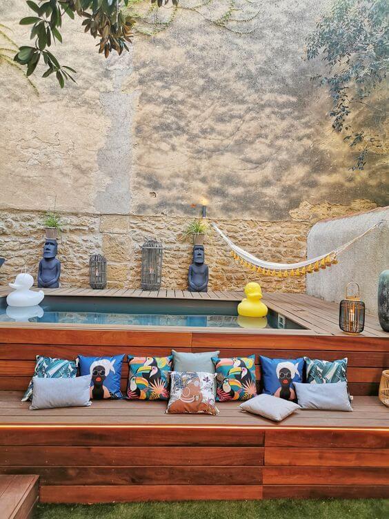 Quintal com piscina elevada e deck de madeira e almofadas estampadas