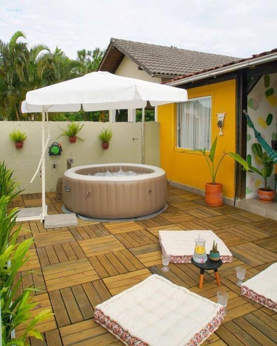 Quintal pequeno com piscina inflável e redonda protegida do sol pelo ombrelone