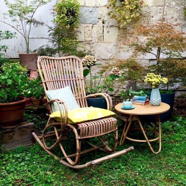 Sacada decorada com plantas e cadeira de balanço de vime