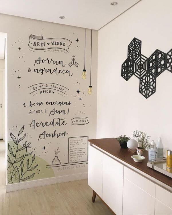 Sala com lettering na parede branco e preta