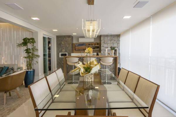 Varanda gourmet decorada com vaso de flor amarela e cadeiras de madeira